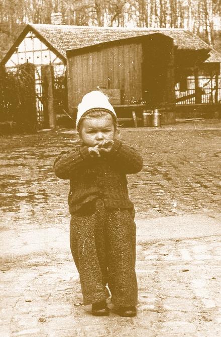 Hier stehe ich als Zweieinhalbjährige vor dem Milchkannenhäuschen auf dem Gutshof. Es ist das einzige Foto, das ich aus dieser Zeit besitze.